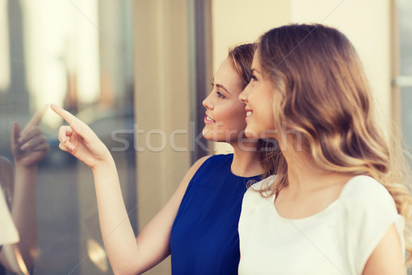 happy young women pointing finger to shop window Stock photo © dolgachov