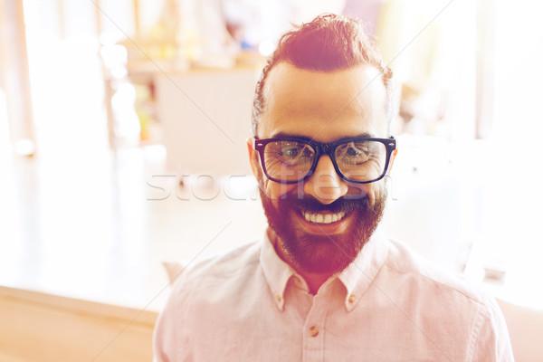 smiling man with eyeglasses and beard at office Stock photo © dolgachov