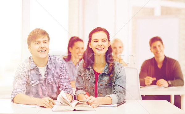 two teenagers with notebooks and book at school Foto stock © dolgachov