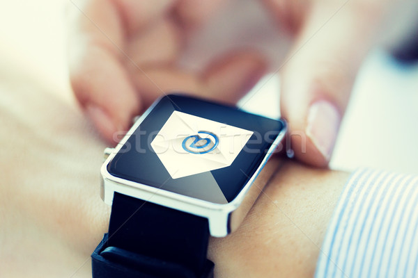 close up of hands with email icon on smartwatch Stock photo © dolgachov