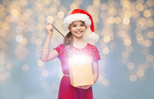 girl in santa hat with gift box and magic wand Stock photo © dolgachov