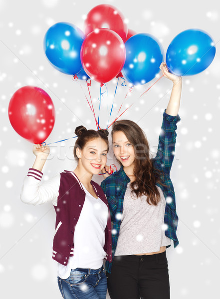 happy teenage girls with helium balloons over snow Stock photo © dolgachov