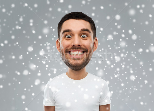 man with funny face over snow background Stock photo © dolgachov