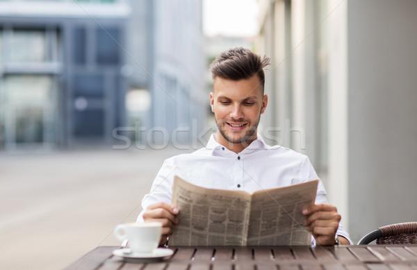 Souriant homme lecture journal rue de la ville café Photo stock © dolgachov