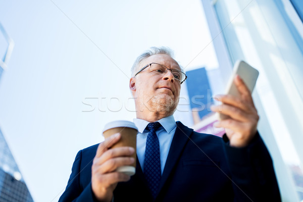businessman with smartphone and coffee in city Stock photo © dolgachov