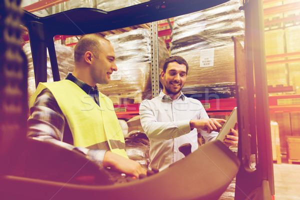 happy men with tablet pc and forklift at warehouse Stock photo © dolgachov