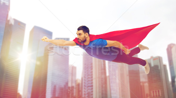 man in red superhero cape flying over city Stock photo © dolgachov