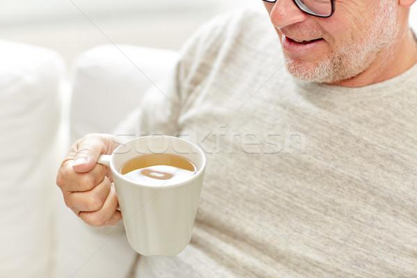 Közelkép boldog idős férfi iszik tea Stock fotó © dolgachov