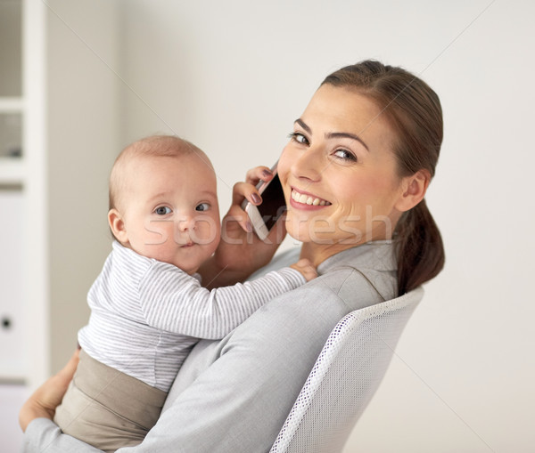 businesswoman with baby and smartphone at office Stock photo © dolgachov