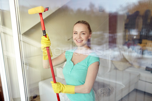 happy woman in gloves cleaning window with sponge Stock photo © dolgachov