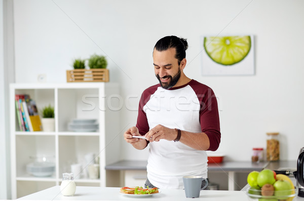 man photographing food by smartphone at home Stock photo © dolgachov