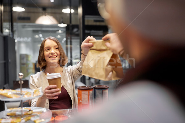 woman taking paper bag from seller at cafe Stock photo © dolgachov