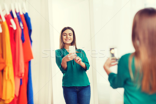 Stock photo: woman with smartphone taking mirror selfie at home