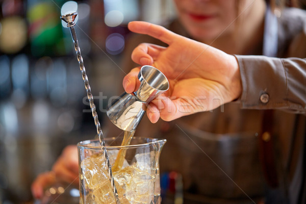 bartender with cocktail jigger and glass at bar Stock photo © dolgachov