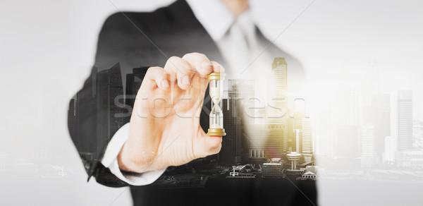 close up of businessman hand holding hourglass Stock photo © dolgachov