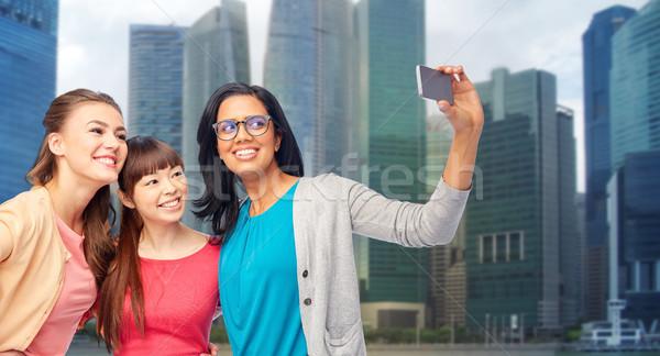 international happy women taking selfie in city Stock photo © dolgachov
