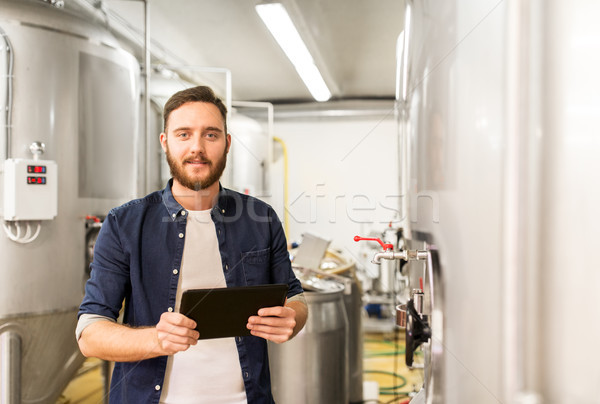 man with tablet pc at craft brewery or beer plant Stock photo © dolgachov