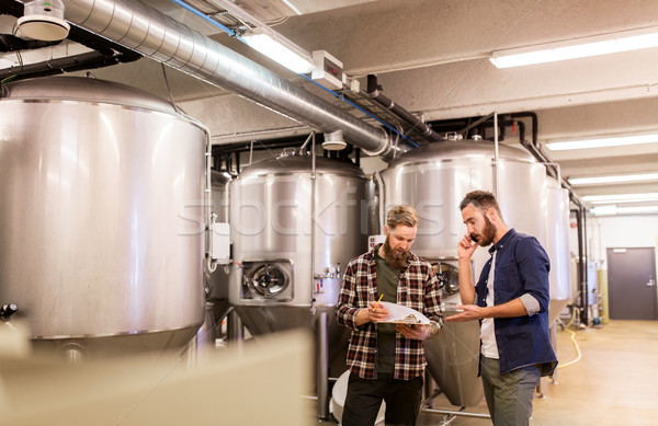 men working at craft brewery or beer plant Stock photo © dolgachov