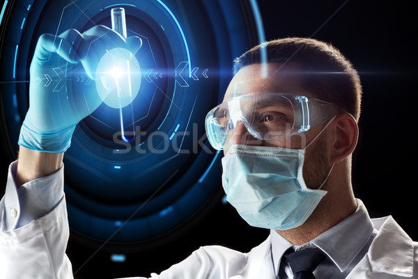 scientist with test tube and virtual projection Stock photo © dolgachov