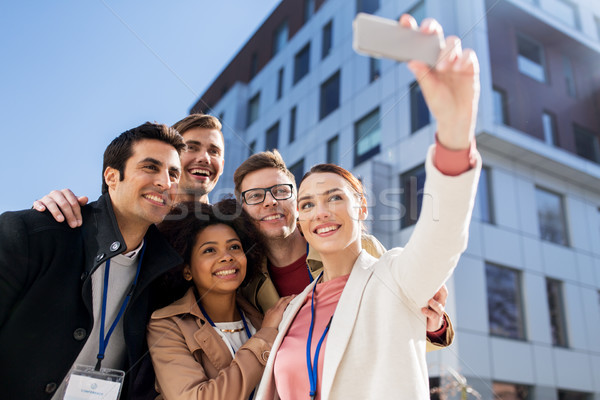 happy people with conference badges taking selfie Stock photo © dolgachov