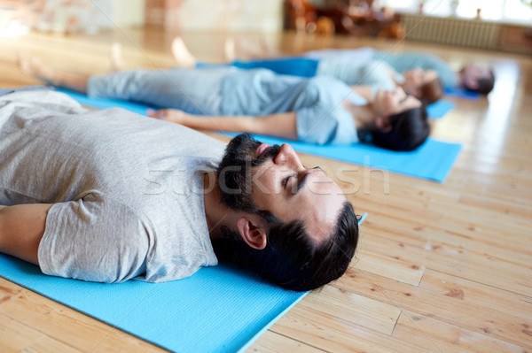 man with group of people doing yoga at studio Stock photo © dolgachov