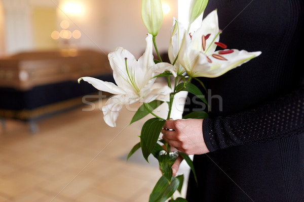 close up of woman with lily flowers at funeral Stock photo © dolgachov