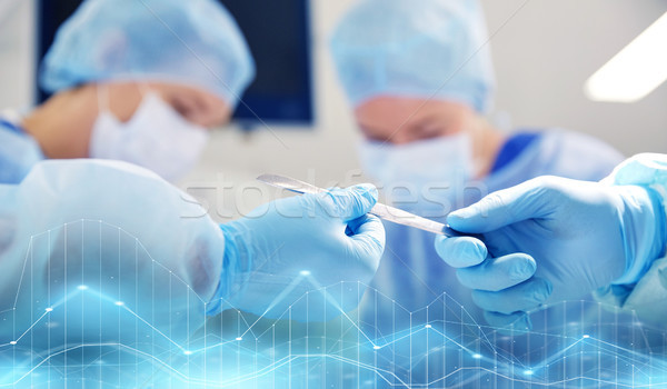 close up of hands with scalpel at operation Stock photo © dolgachov
