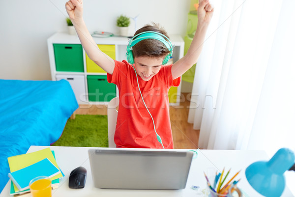 Menino fones de ouvido jogar jogo vídeo laptop tecnologia Foto stock © dolgachov