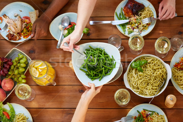 people at table with food eating green beans Stock photo © dolgachov