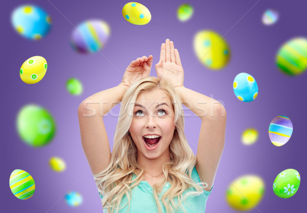 happy woman making bunny ears over easter eggs Stock photo © dolgachov