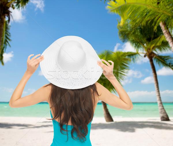 Kadın oturma mayo şapka yaz tatili plaj Stok fotoğraf © dolgachov