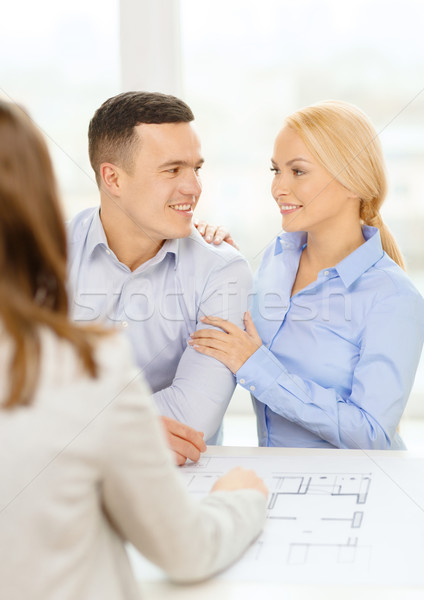 smiling couple looking at blueprint Stock photo © dolgachov