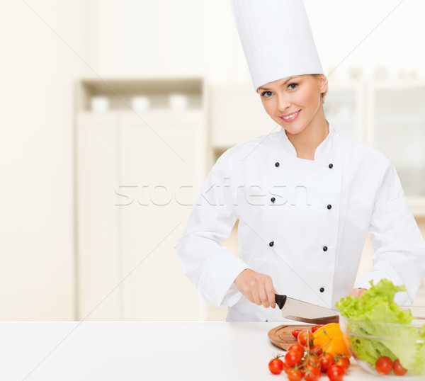 Stock photo: smiling female chef chopping vagetables