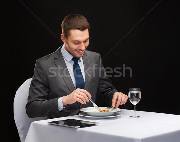 Mosolyog férfi táblagép eszik főétel étterem Stock fotó © dolgachov