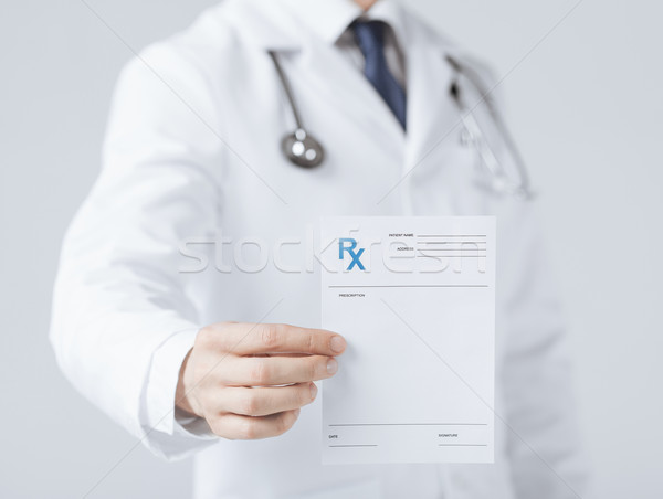 male doctor holding rx paper in hand Stock photo © dolgachov