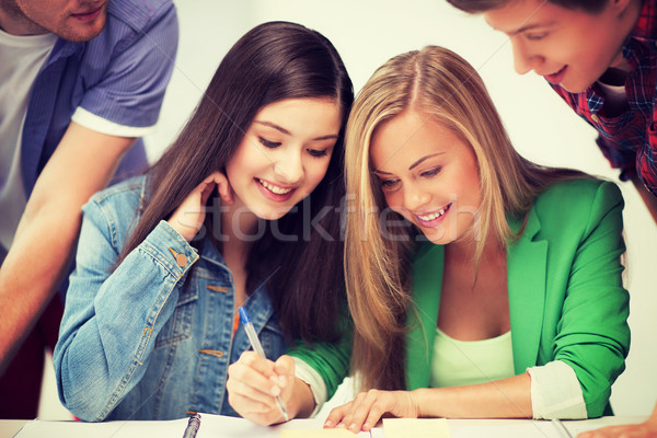 Stock photo: students pointing at notebook at school