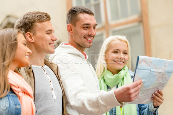 group of friends with map exploring city Stock photo © dolgachov