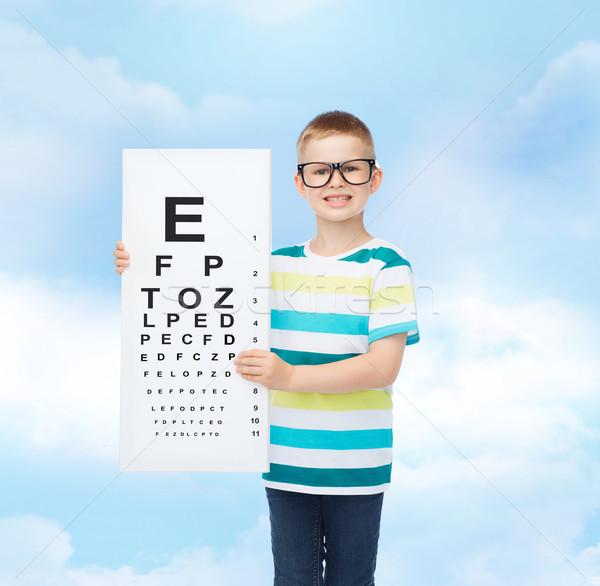 smiling boy in eyeglasses with white blank board Stock photo © dolgachov