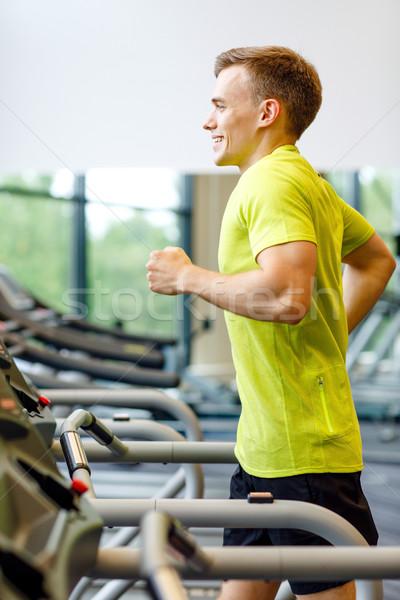 Glimlachend man tredmolen gymnasium sport Stockfoto © dolgachov