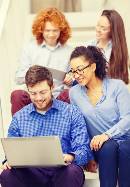 team with laptop and tablet pc on staircase Stock photo © dolgachov