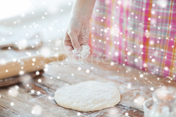 close up of woman hand sprinkling dough with flour Stock photo © dolgachov