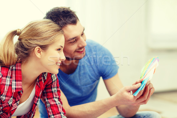 smiling couple looking at color samples at home Stock photo © dolgachov