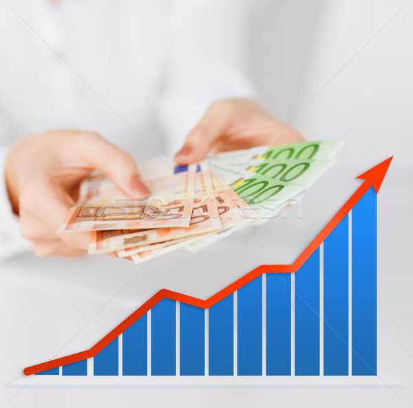 Stock photo: close up of woman hands with chart and money