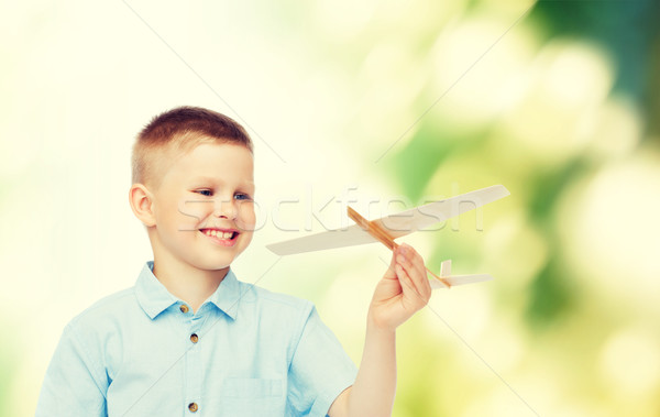 Stock photo: smiling little boy holding a wooden airplane model