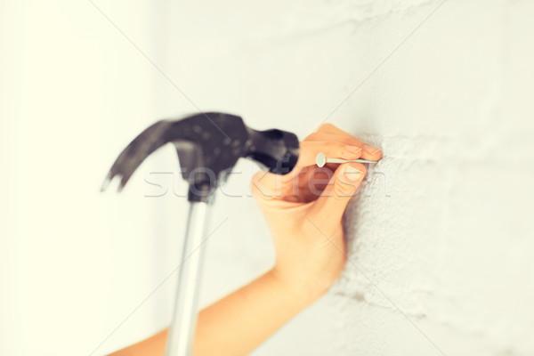 architect hammering nail in wall Stock photo © dolgachov