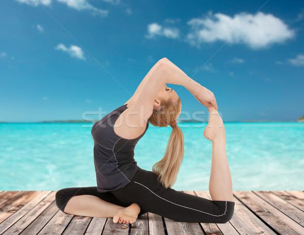 happy young woman doing yoga exercise Stock photo © dolgachov