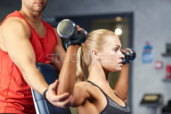 man and woman with dumbbells in gym Stock photo © dolgachov