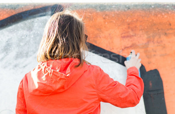 woman drawing graffiti with spray paint from back Stock photo © dolgachov
