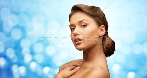 woman with bare shoulders over blue lights Stock photo © dolgachov