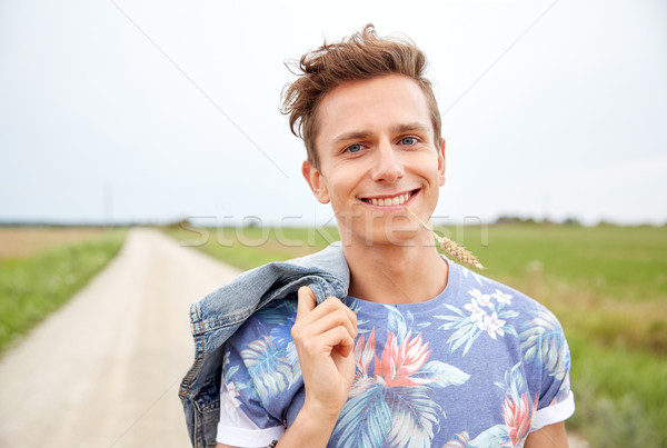 smiling young hippie man on country road Stock photo © dolgachov